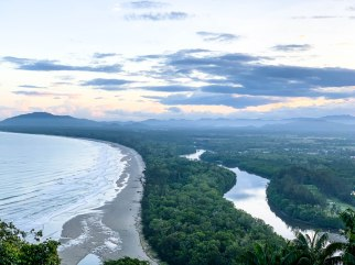 View from hilltop lookout at Rasa Ria Resort towards sea and mountains at sunrise